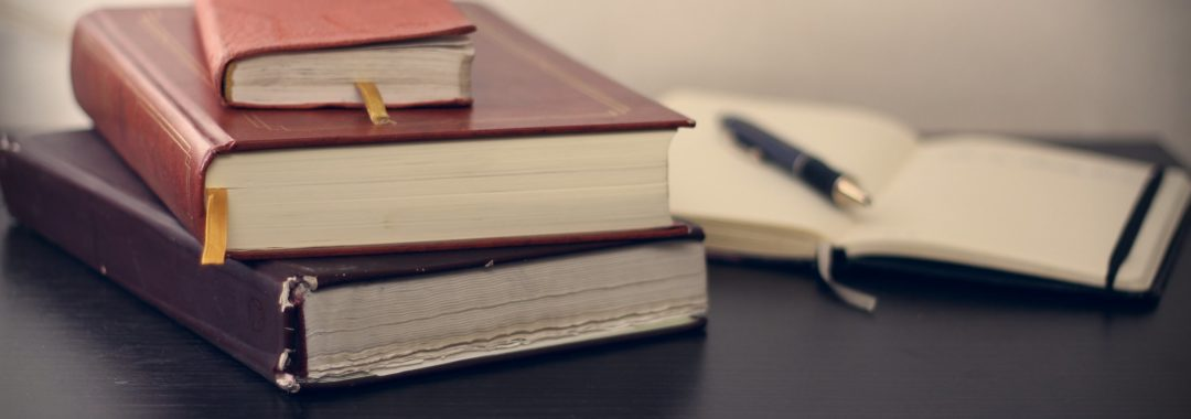 Stack of books with pen and notebook in background