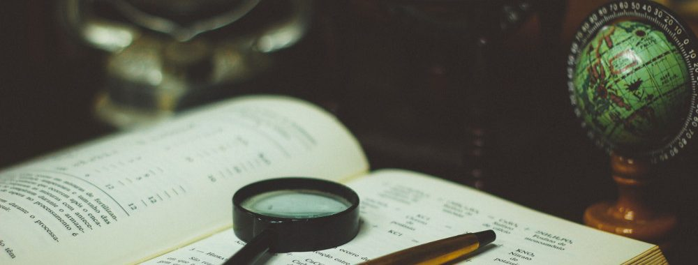 Magnifying glass and pen resting on top of a book