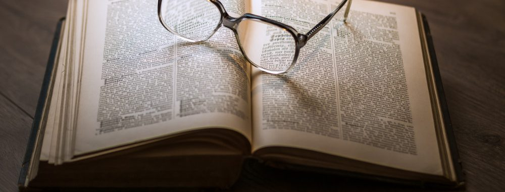 A pair of glasses sitting on top of an open book