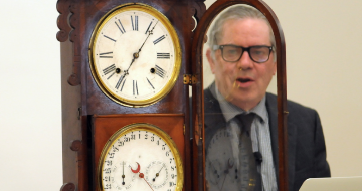Appraiser Mark Moran sitting next to an antique clock