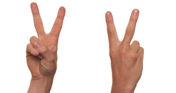 Two hands performing sign language gestures.