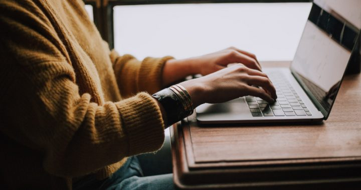 Torso of person in a yellow sweater typing on a laptop