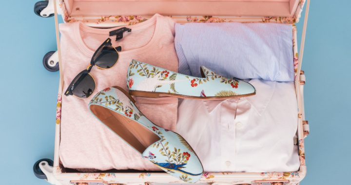 Open pink suitcase with clothing, sunglasses and shoes