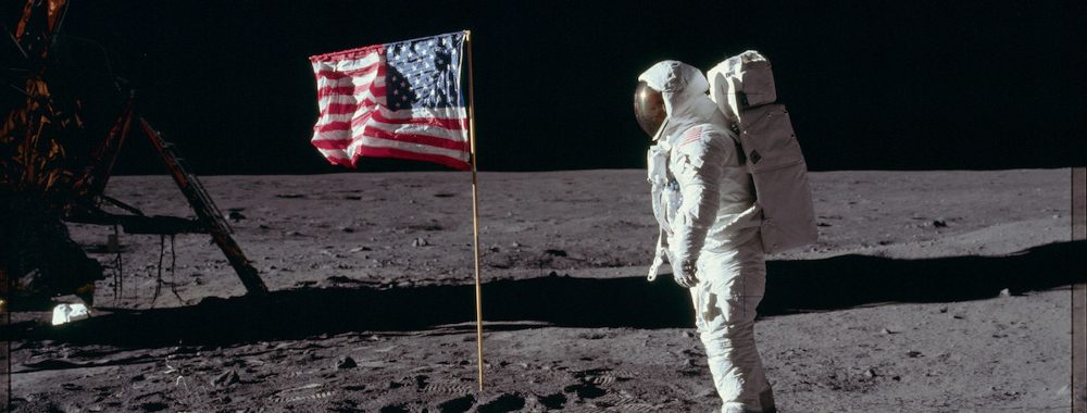 Astronaut on moon next to U.S. flag