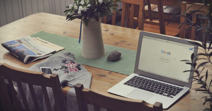 Open laptop on a table next to flowers, a shirt, a newspaper and a phone