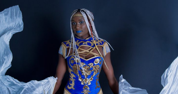 Woman in blue and gold performance outfit with dancing silks.
