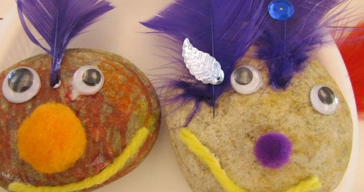 Two rocks with wiggly eyes and feathers