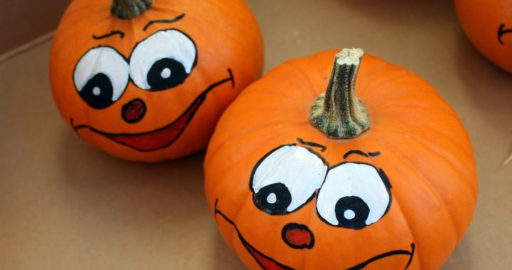 2 small pumpkins with smiley faces painted on