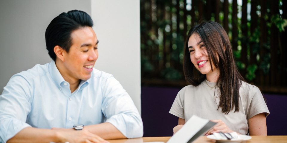 Two people at a table discussing an open book.