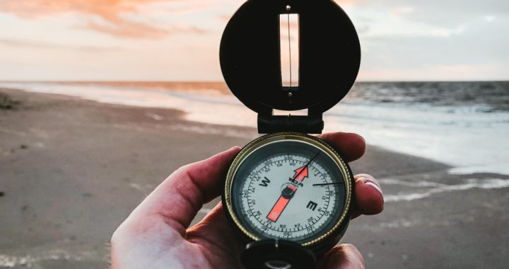 Hand holding a compass by the shoreline of the ocean