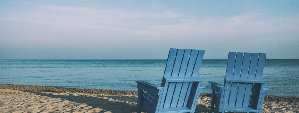 Two blue chairs sitting on the beach