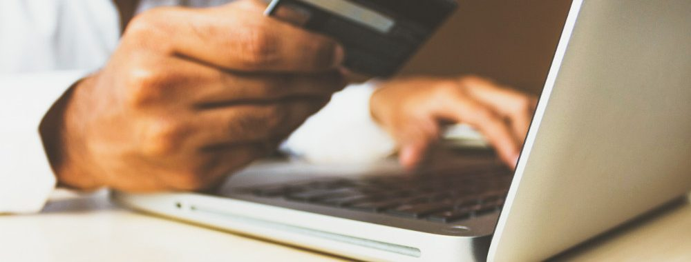 Hands typing on a laptop while holding a credit card