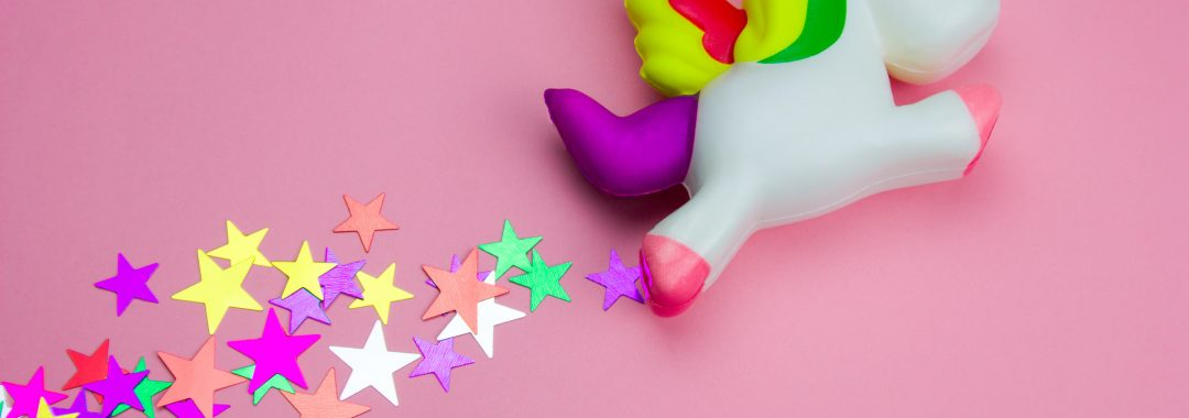 squishy toy unicorn on a pink background with a trail of stars