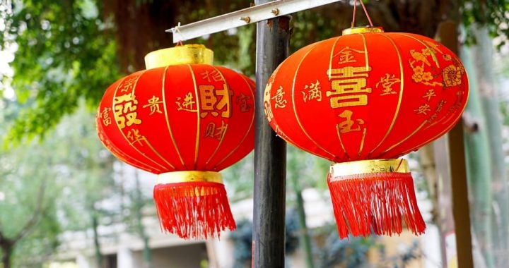 two red and yellow Chinese lanterns hanging on a post