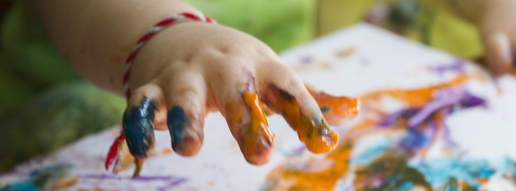 A child finger painting on a canvas with orange paint
