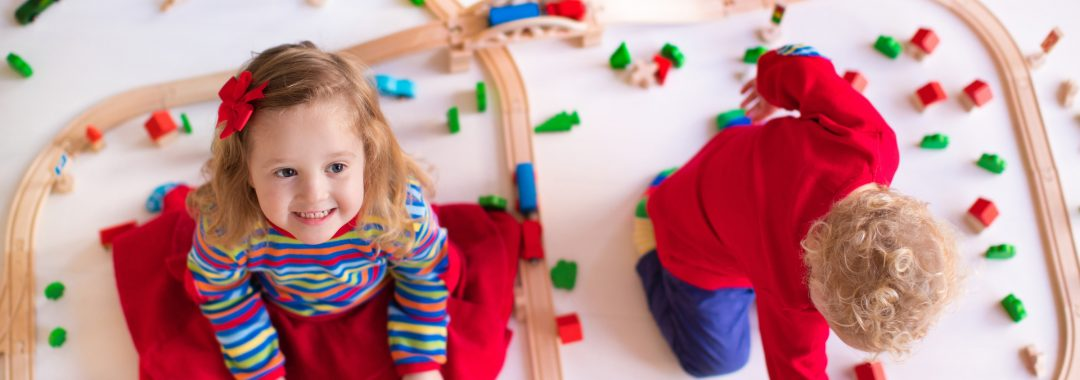 Two children playing with train set