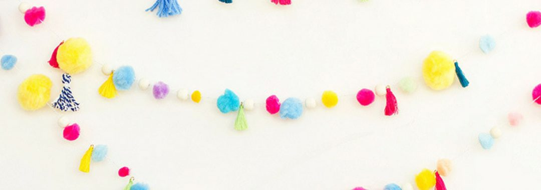 3 Colorful strands of garland with pom-poms and tassels hanging from it