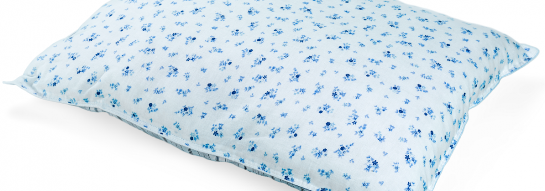 White pillow with blue flower pattern